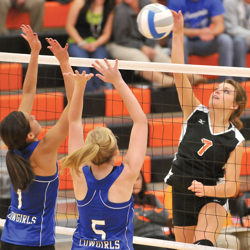 Ellie Rabenberg hits a kill attempt as Julie Blue Arm (1) and Marissa Lyon (5) of Lemmon try to defend. The Lady Tigers beat the Cowgirls 3-2 at Mobridge-Pollock High School Gymnasium on Thursday.