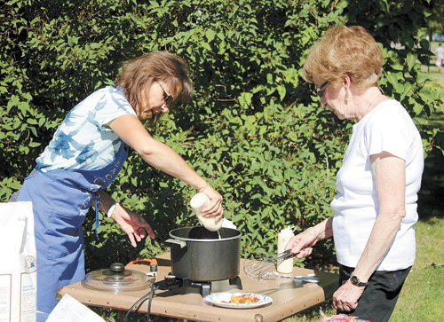 Jan Sayler (left )and Theresa Hazel make funnel cakes to sell at Arts in the Park, held Saturday at City Park. The cakes raised $300 for the Rotary Club.