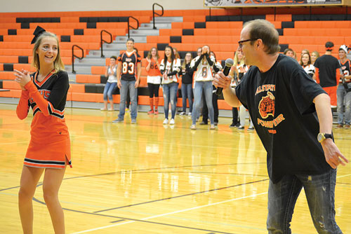 """Staff of the Mobridge Pollock School District, led by Jeremy Storly (right) surprised students, including cheerleader, Briana Monsen, with a rendition of Queen's """"We are the Champions"""" Friday at the homecoming pep rally at the MP High School gym. The the pep rally followed the annual homecoming parade and was followed by the Tiger Olympics, all part the homecoming week activities last week."""