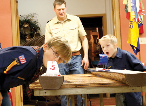 The annual Cub Scout rain gutter regatta was held on Tuesday, Nov. 15, at the Zion Lutheran Church in Mobridge. Participating in one of the races are (left) Sebastian Oster, son of Taylor and Harmony Oster and (right) Zaiden Lindeman, son of Brian and Ashley Lindeman. Supervising the race is (back) Scoutmaster Dr. Josh Henderson.