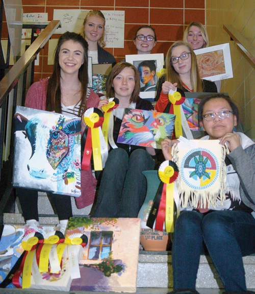 Seven artists teamed to win the first-place trophy at the Lakota Nation Invitational Art Show in Rapid City. Pictured with their art pieces and ribbons are: (back from left) Autumn Schlomer, Kailey Jerome and Keiara Lesmeister; (middle from left) Danielle Beadle, Amy Kulm and Kiersten Stickney; (front) Tamiera Garter. Beside Garter is the first-place trophy.