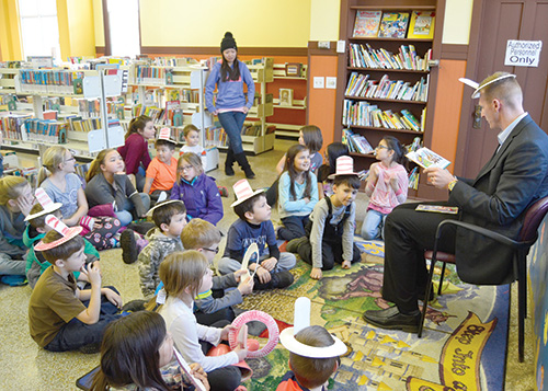"Mayor Jamie Dietterle (right) was one of a several local personalities that read to children Thursday, March 2, for the ""Reading Across America"" celebration. The children listened to favorite books and did crafts including making 'Cat in the Hat' hats, that they wore during story time."