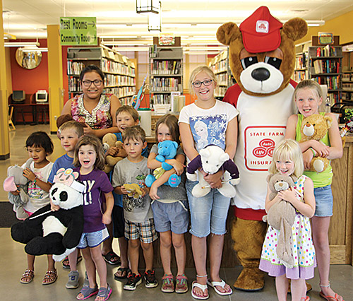 Children participated in the Teddy Bear Picnic July 10 at the A. H. Brown Library. In front from left: Ava Flying Horse, Nathan Caughlin, Maria Caughlin, Kylar Wessel, Zentaya Wessel, Grace Fulkerson, Leah Bohlander, and Elsy Larsen. In back: Fawnarae Halfe, Tyler Roebuck, and the State Farm Bear.