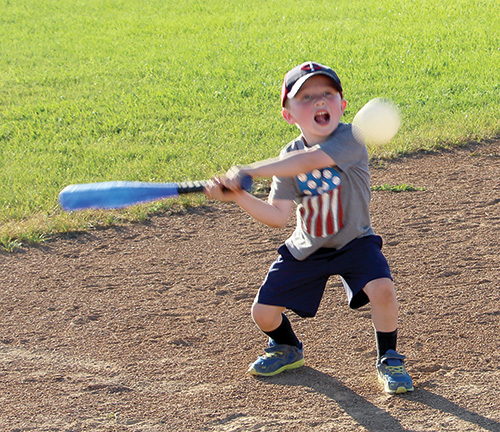 Jared Steiger practices his batting skills while his dad prepares for his own softball game against Eureka on Thursday, July 13. Jared's parents are Sadie and Jamey Steiger.