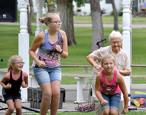 Irene Kosters, (back right) shows the younger generation Laney Blankartz, Kyah Feyereisen and Chloe Blankartz how to the do the chicken dance. The group was enjoying the music of Phil Baker Thursday, July 27, at the city park.Kyah is the daughter of Diedra and Justin Feyereeisen and Laney and Chloe are the daughters of Desiree Blankartz, all of Mobridge. The Phil Baker show was sponsored by the A. H. Brown Library, A. H. Brown Library Foundation from the Barbara Nolop Fund, and the South Dakota Arts Council.The Arts Council must be listed as part of the grant agreement.